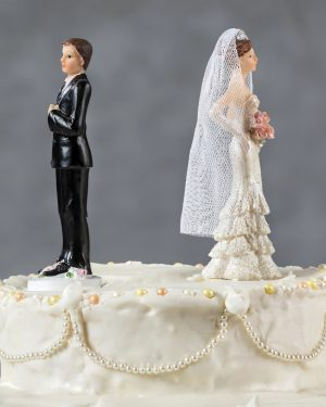 Man and woman cake toppers facing opposite directions on white wedding cake