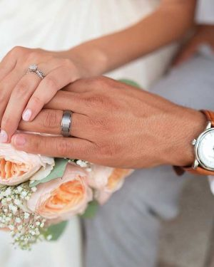 Female hand on top of male hand with ring on top of bridal flowers