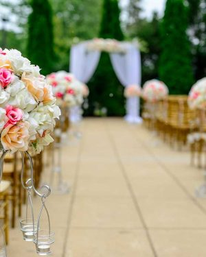 Isle at wedding with flower stands leading to trellis