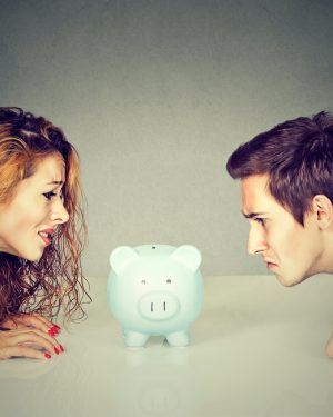 Couple Staring at Piggy Bang to Split Assets
