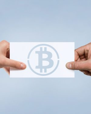 Two hands holding piece of paper with Bitcoin symbol.