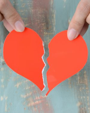 one hand holding a torn red paper heart and the other hand holding the other half