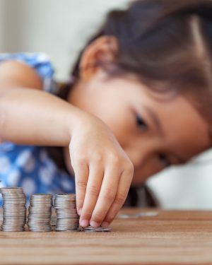 Young Girl Stacks Rows of Nickels