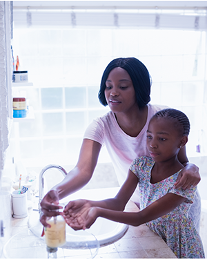 Mother Helps Young Daughter Wash Hands for COVID-19 Prevention