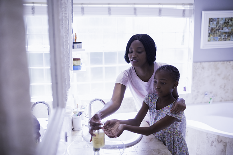 Mother Helps Young Daughter Wash Hands in Bathroom for COVID-19 Prevention - Horizontal Photo