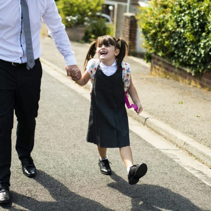 Business man with slacks and tie holds hand of young daughter with pigtails