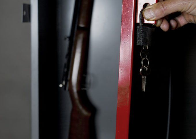 Human hand opening a metal gun safe with a gun inside, studio cropped shot